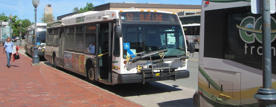 "A Codiac Transpo city bus sits at the curb awaiting passengers, while running on the Route 52 ""Blue Line"""