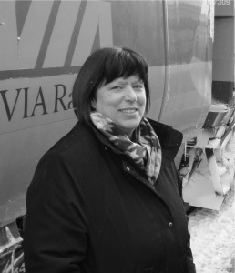 Woman with dark hair, in a winter dress coat, standing next to a VIA Rail traincar.