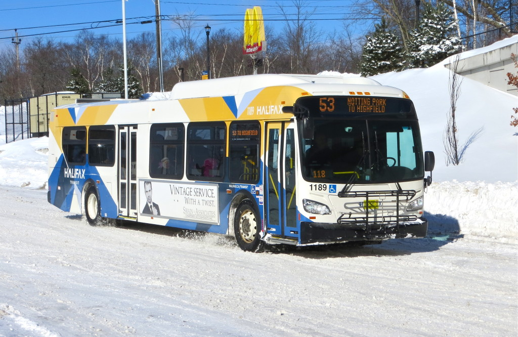 A clean, modern looking bus with yellow and blue X-shaped markings on white, drives through the snow in the centre of the image.
