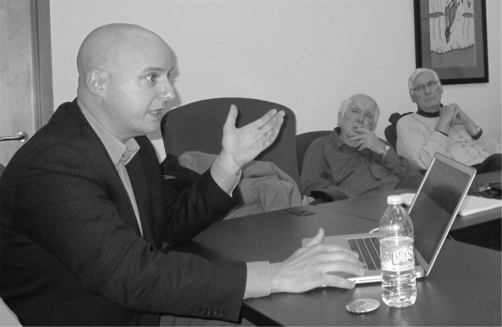 Dr Yves Bourgeois at a table, in discussion.