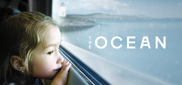 A young girl looking out the window of a train, passing by a coastal scene with snow in the air. Text reads The Ocean.