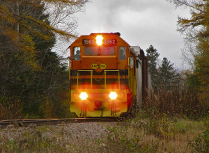 An orange and yellow train with bright headlights heads directly towards the viewer under cloudy fall skies.