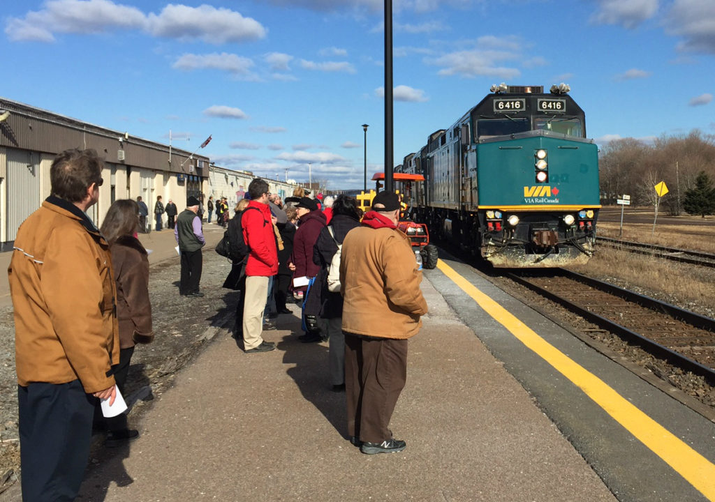 A group of people wait on a station platform as a teal VIA passenger train arrives