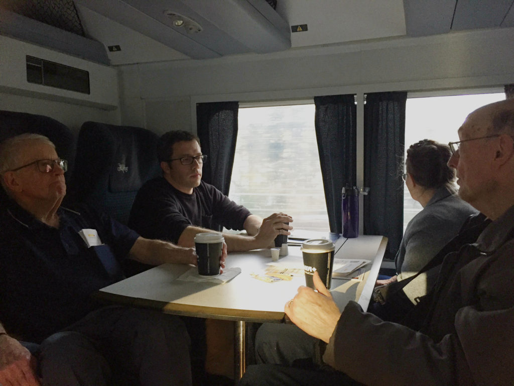 Four people sitting in opposing seats across a table inside a train car, as scenery flies by outside the window