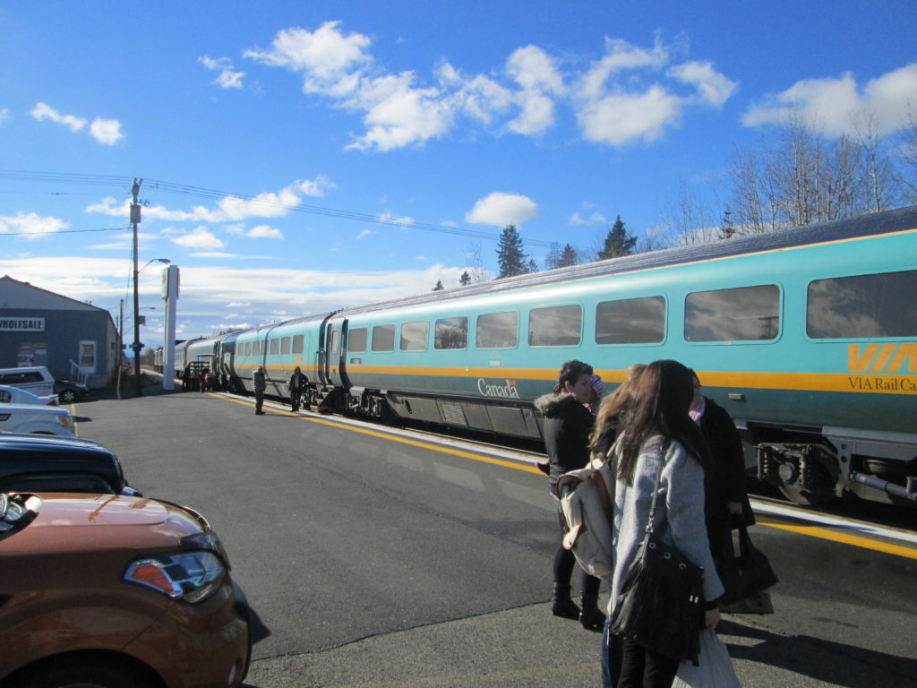 Passengers stand on the platform next to VIA's two-tone teal Renaissance passenger cars